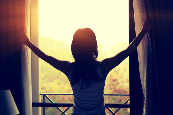 Woman opening curtains in the morning and looking out with hope to illustrate that counseling works!